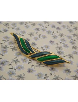 a-lovely-early-to-mid-90s-modern-stylized-bow-design-jewelry-brooch-made-in-goldtone-metal-and-decorated-with-shiny-blue-green-enamel by vintagejewelleryetc