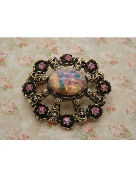 a-gorgeous-large-oval-vintage-jewelry-brooch-made-in-openwork-goldtone-metal-with-a-large-faux-opal-surrounded-with-sparkly-pink-stones by vintagejewelleryetc